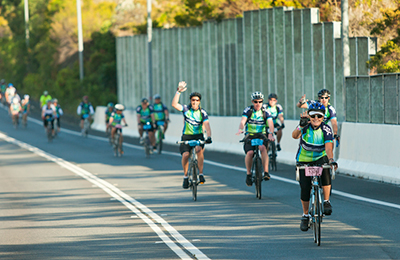 A long line of cyclists riding on a highway. There are no cars.