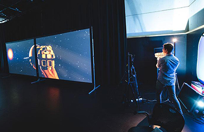 A man holding a small puppet that is being projected onto a screen in the distance.