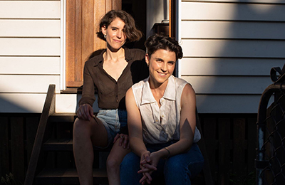 Samantha and Karina Seljak sitting together on the front steps of a house. They are wearing casual clothes and smiling at the camera.