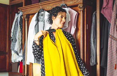 woman holding up a yellow dress against her body and looking in a mirror to see how it looks. She is standing next to a closed wardrobe with clothes hung on clothes hangers hung to the outside.