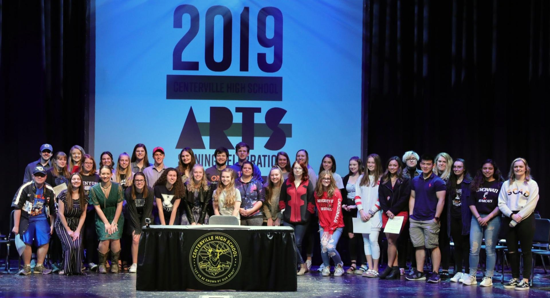 Image of large group of students on stage with sign that reads 2019 Arts Signing Celebration