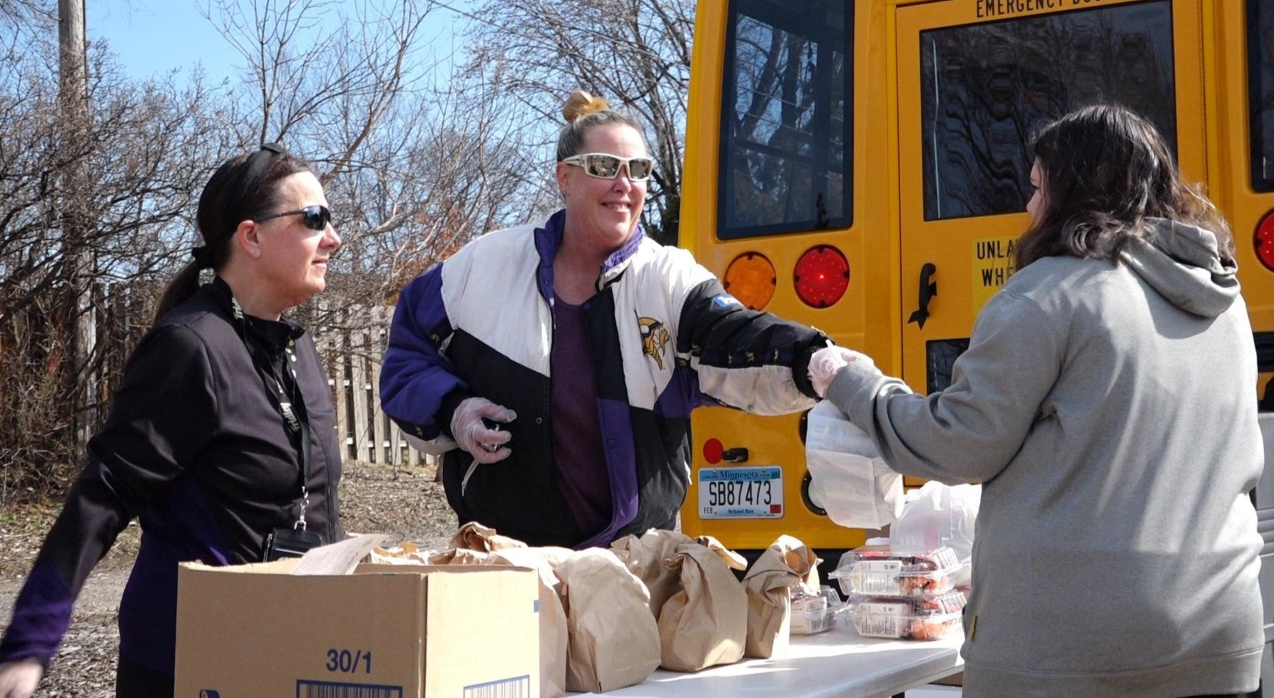 Nutritional Services staff handing out grab-and-go meals