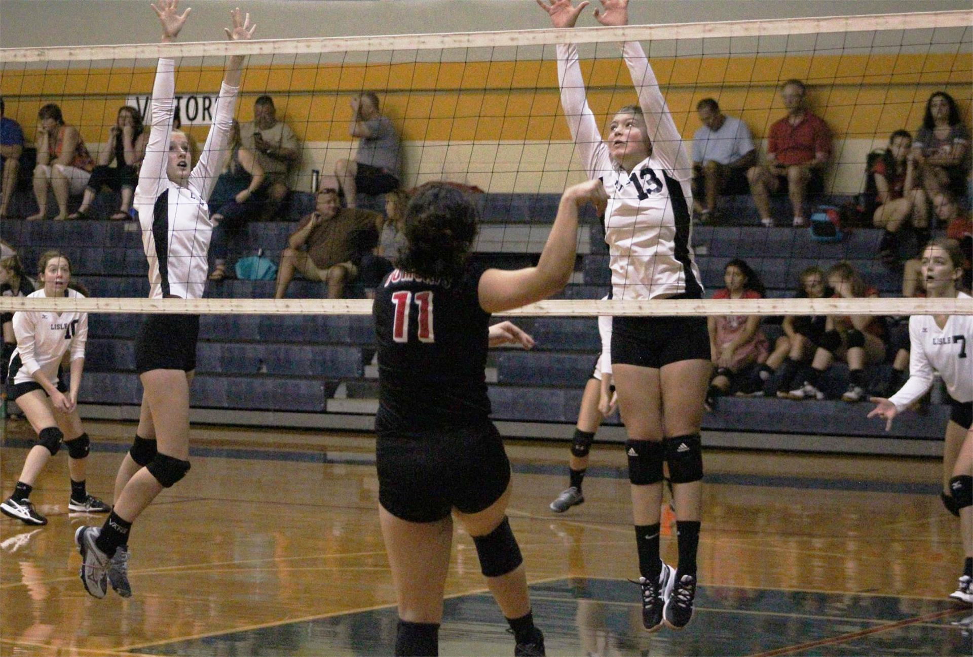 LHS Volleyball players block at the net