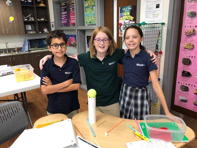 students displaying their tennis ball tower