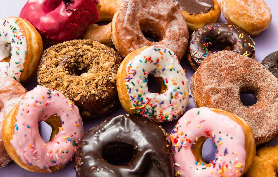 Picture of a variety of donuts - mostly glazed and some with sprinkles and some with nuts.