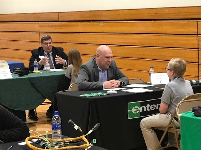 Picture of a student sitting across from an adult from Enterprise during Cole Professional Interview Day. In the background is another student intervieiwng with another adult volunteer.