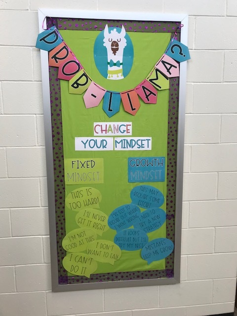 """Image of a bulletin board with light green fabric as the background with a cartoon paper cut out of a llama head with a bow tie with the lettering """"Prob-llama? written in pennant style. Underneath are the words, """"Change Your Mindset"""" with the words """"Fixed Mindset"""" and """"Growth Mindset"""" written underneath with bubbles like """"This is too hard"""", """"I;ll never get it right: under Fixed Mindset and """"This may requre some effort: and I've got to try a different strategy"""" under """"Growth Mindset"""""""