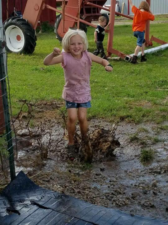 Picture of a young lady in the midst of jumping into a mud puddle at the county fair. She is wearing boots, a tank top, and shorts as well as a giant smile.
