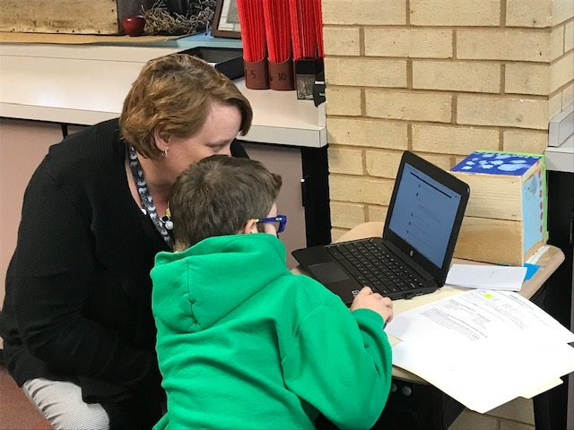 Child hunkered down over a computer with his mother during recent Student Share Their Learning event.