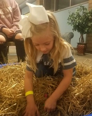 girl digging in the hay