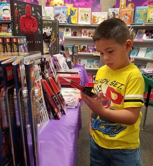 boy looking at a book at the book fair