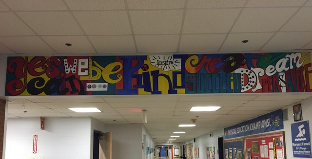 Colorful artwork above the entrance to the hallway that states ''Yes we can be kind, creative, inspiring, succeed, dream, perserevre