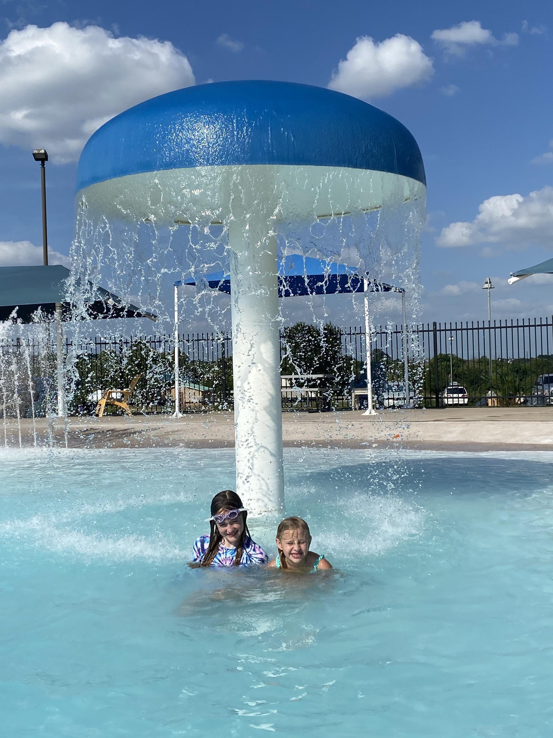 kids under mushroom fountain in pool