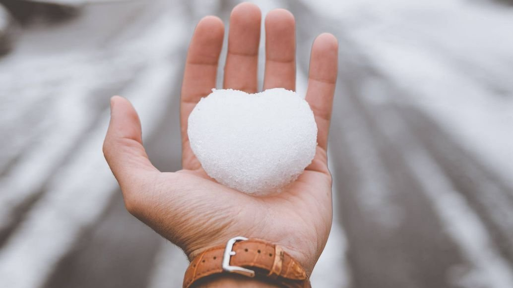 Bare hand holding heart-shaped snow ball