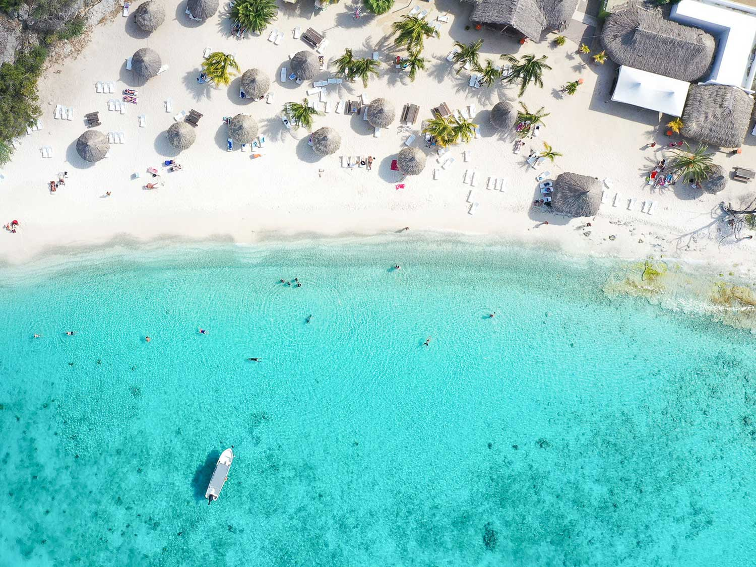 An aerial view of an island beach resort with crystal clear waters.