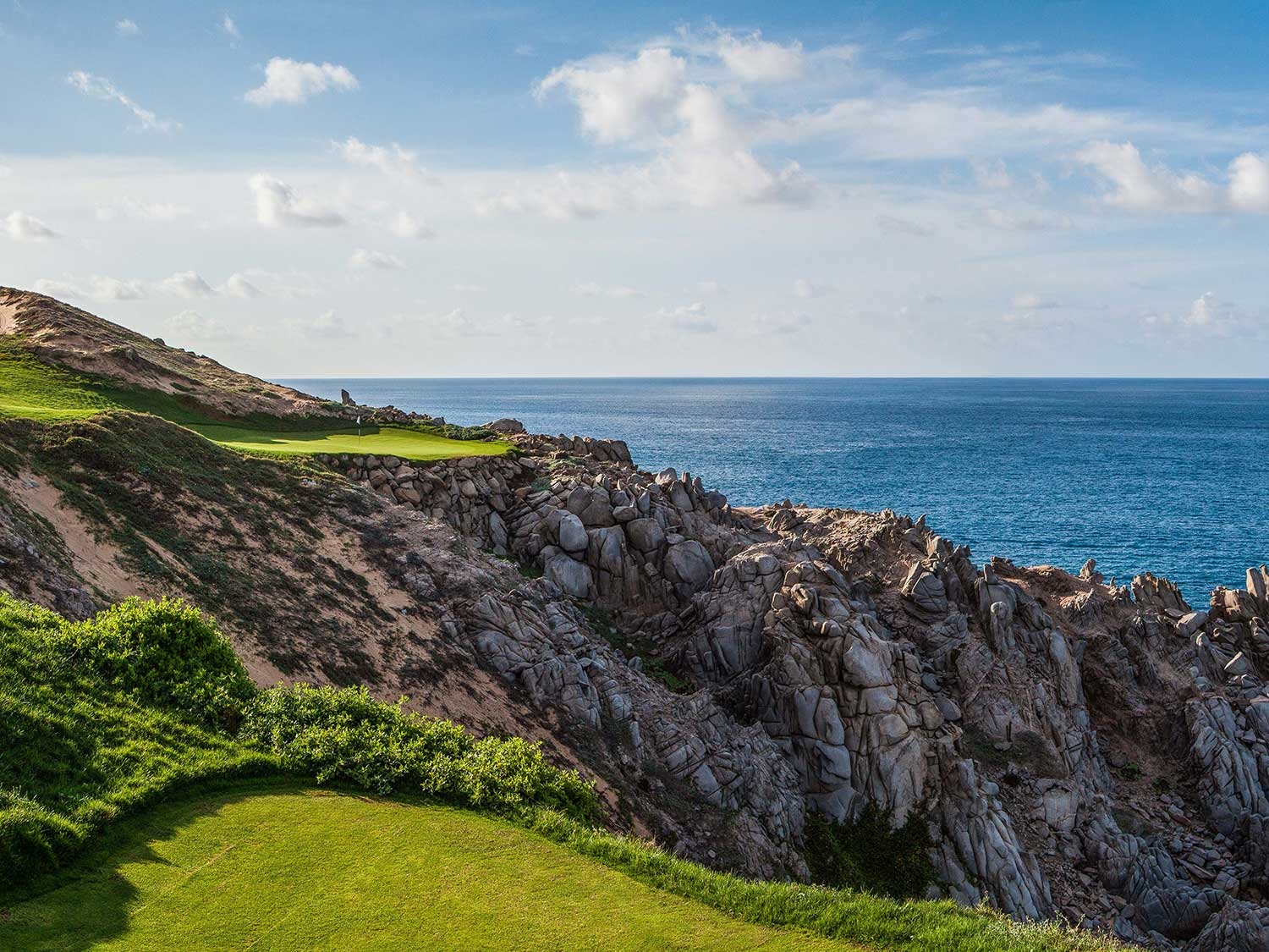 A vibrant green golf course against a rocky, oceanside.
