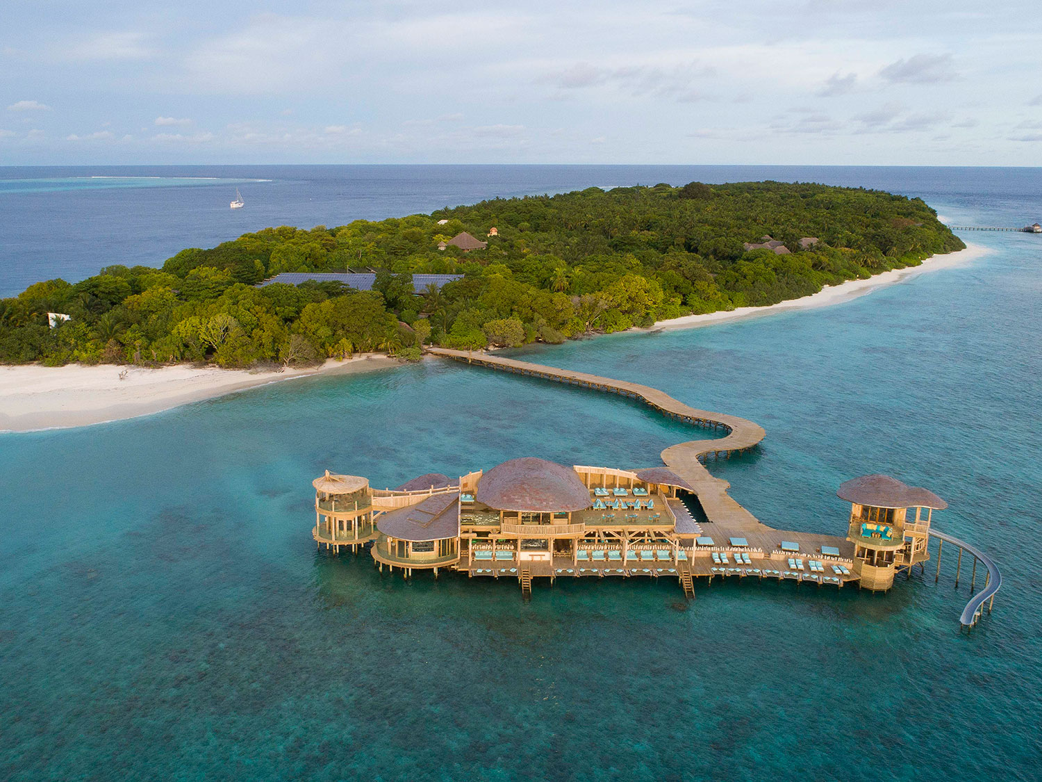 A lush green island surrounded by the ocean. An island pier resort branches off the island.