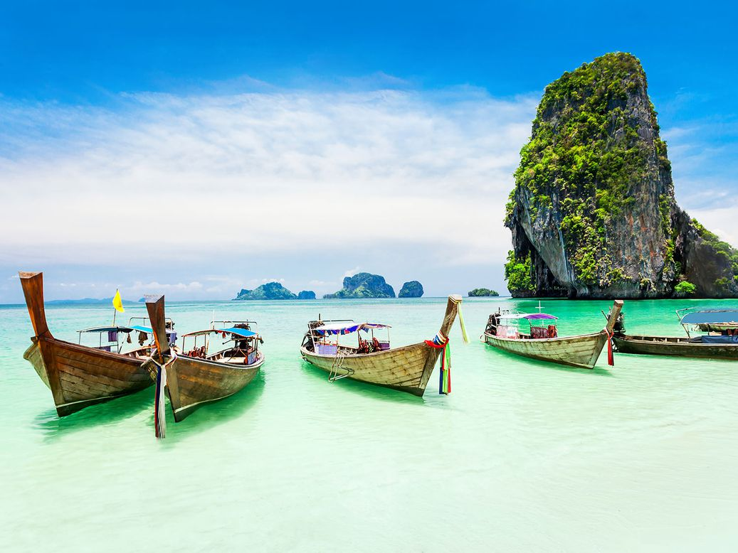 A lineup of Thai ferry boats anchored in the ocean off the shore of the beach.