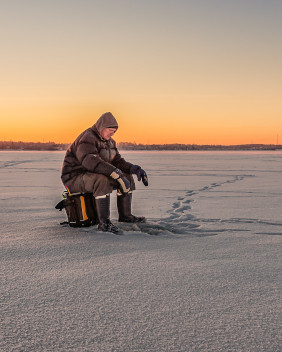 Man ice-fishing on the frozen Bay of                               Finland.