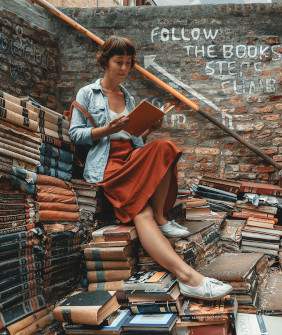 Women reading books on a pile of                               books