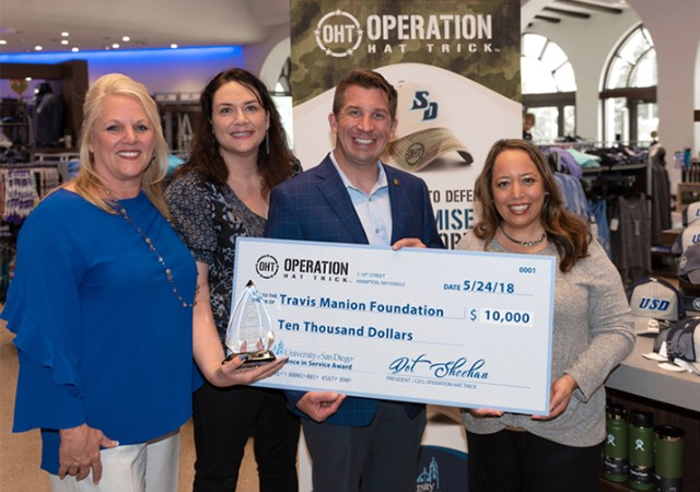 USD employees pose with a large check made out to the Travis Manion Foundation